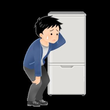 冷蔵庫の前で悩む男性